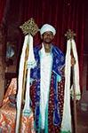 Kněz.   Kněz Etiopské ortodoxní církve vjednom zunikátních kamenných kostelů vLalibele. Etiopské ortodoxní křesťanství má svá mystická specifika. Svatí muži, ve společnosti nebývale uznávaní, putují po zdejší hornaté krajině. Bubnování při bohoslužbách, tajemně postavené kostely, záhadně zdobené kříže abájné spojení sJeruzalémem, to vše činí zetiopského křesťanství velmi zajímavou odnož světově nejrozsáhlejšího náboženství vyznávajícího jednoho pravého, živého Boha. Zatímco vhorách žije hluboká spiritualita křesťanství, vsuchých nížinách vítězí islám. Vtropických deštných pralesích na jihozápadě země potom vévodí animismus, tedy voodoo.   (Etiopie)