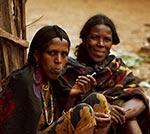 Na trhu.   V podhůří etiopských hor. Když asijští obchodníci dovezli na východoafrické pobřeží zindonéských ostrovů banány ajamy, jež se daly pěstovat voblastech, kde značnou část roku prší, zaznamenala Afrika první populační výbuch, při němž se přebytky obyvatel šířily do vlhčích lesních oblastí. Během tisíce let zaplnilo západoafrické černošské obyvatelstvo východní ajižní Afriku, vpodstatě celou oblast na jih od Sahary. Přistěhovalci se mísili spůvodním obyvatelstvem východní ajižní Afriky. Jeho pozůstatkem jsou Křováci - Bushmani - žijící vpoušti Kalahari, lid se žlutohnědou pokožkou, který snad vpradávných dobách obýval celou východní část Afriky až po Kapsko. Byli to primitivní lovci, kteří byli bojovnými pasteveckými kmeny vytlačeni do nehostinné pouště. Přistěhovalí černoši se snimi mísili avytvořili to, čemu říkáme bantuské národy.   (Etiopie)