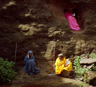 Barevní svatí muži.   Svatí muži studují ve skále Písmo. Své krásné kříže mají opřené vedle sebe.   (Etiopie)