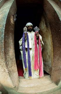 Etiopský kněz.   Kněží hrdě střeží vchody do kamenných skvostů světové architektury. Snad již fakt, že vzácné adrahé klenoty zinteriérů nikdo nevykradl, což je vAfrice celkem běžná věc, svědčí otom, že jim vtom pomáhá Bůh.   (Etiopie)