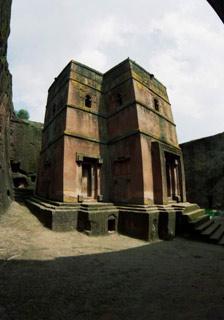 Z nitra.   Velkolepý kostel St. George je do kamenné země vytesán vpůdorysu kříže. Také všechny doplňky aozdoby nesou podobný tvar. Dvoupatrová budova zjedné masy kamene je jakoby zapuštěna na dno vyhloubené díry.   (Etiopie)